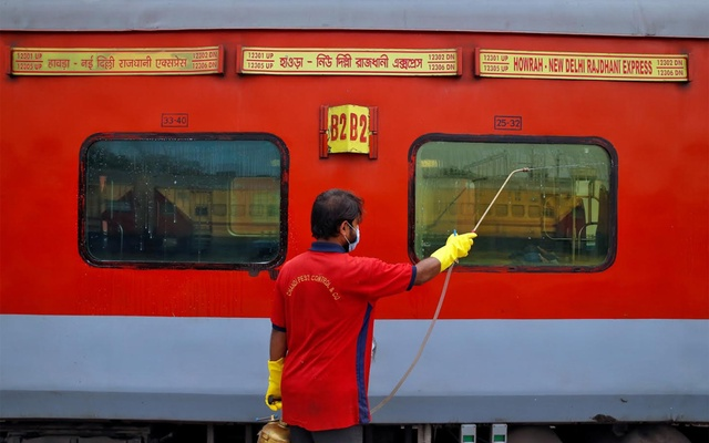 A worker disinfects the exteriors of a passenger train parked at a railway yard as a preventive measure against coronavirus, on the outskirts of Kolkata, India, March 16, 2020. Reuters
