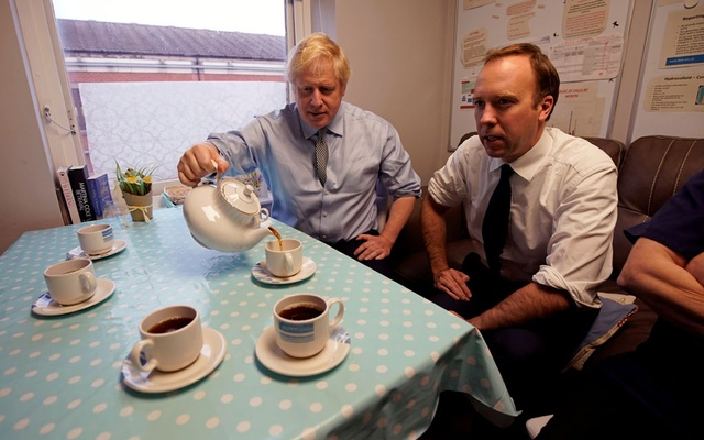 FILE PHOTO: Britain's Prime Minister Boris Johnson and Health Secretary Matt Hancock have tea with members of staff as they visit Bassetlaw District General Hospital in Worksop, Britain November 22, 2019. Picture taken November 22, 2019. Christopher Furlong/Pool via REUTERS//File Photo
