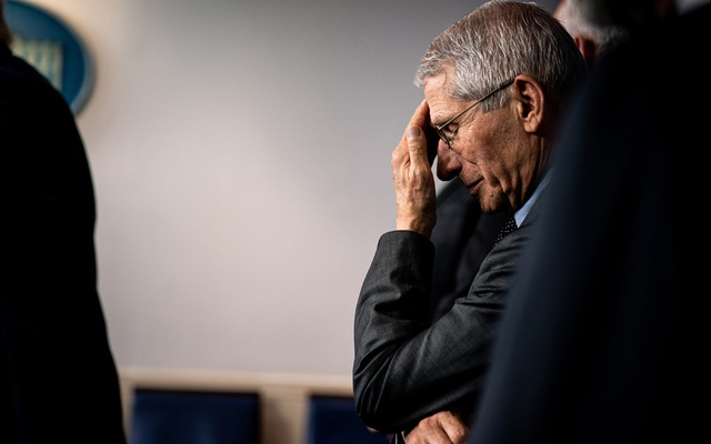 """FILE - Dr. Anthony Fauci, the director of the National Institute of Allergy and Infectious Diseases, rubs his forehead after a President Donald Trump referred to the """"Deep State Department"""" during a coronavirus briefing at the White House in Washington, March 20, 2020. Fauci, the administration's most outspoken advocate of emergency virus measures, has become the target of claims that he is mobilising to undermine the president. (Erin Schaff/The New York Times)"""