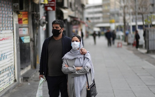 A couple wear protective face masks, amid fear of coronavirus disease (COVID-19), as they walk at Enghelab square, in Tehran, Iran March 26, 2020. WANA (West Asia News Agency)/Ali Khara via REUTERS