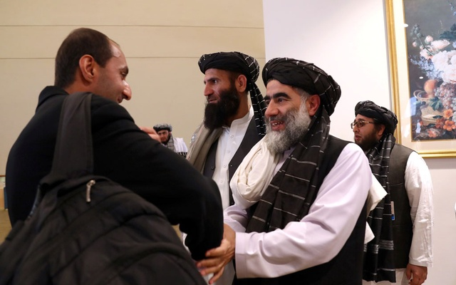 FILE PHOTO: Members of Afghanistan's Taliban delegation (R) gather ahead of an agreement signing between them and US officials in Doha, Qatar, February 29, 2020. REUTERS/Ibraheem al Omari/File Photo