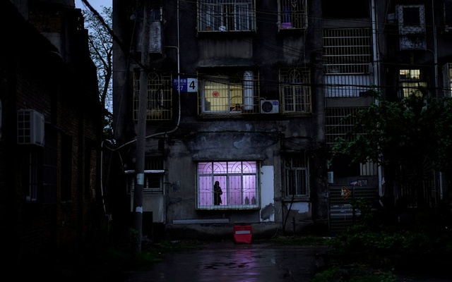 man stands at a window at a residential community in Jingzhou, after the lockdown was eased in Hubei province, the epicentre of China's coronavirus disease (COVID-19) outbreak, March 26, 2020. REUTERS