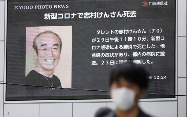 A man wearing a protective face mask walks past in front of a huge screen reporting death of Japanese comedian Ken Shimura, who had been hospitalised after being infected with the new coronavirus, in Osaka, western Japan March 30, 2020. REUTERS