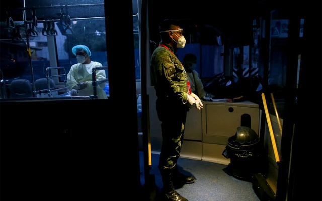A soldier waits for health workers to board a free shuttle service following the suspension of mass transportation to contain the spread of coronavirus disease (COVID-19), in Quezon City, Metro Manila, Philippines, Mar 20, 2020. REUTERS