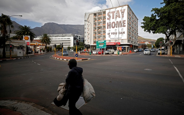 FILE PHOTO: A man walks past a poster covering the side of a building ahead of a 21 day lockdown aimed at limiting the spread of coronavirus disease (COVID-19), in Cape Town, South Africa, March 26, 2020. Reuters