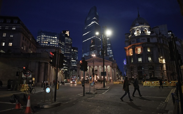Scant few pedestrians walk in London's Financial District nearly empty of activity due to the coronavirus pandemic, March 16, 2020. The New York Times