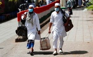 Men wearing protective masks walk as they carry bags, amid concerns about the spread of coronavirus disease (COVID-19), in Nizamuddin, area of New Delhi, India, Mar 31, 2020. REUTERS