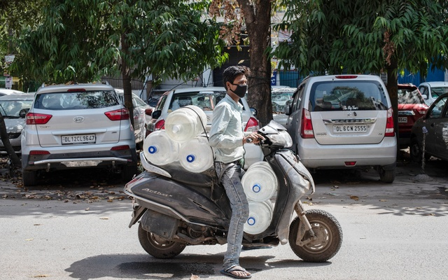 Arjun Chauhan uses his motor scooter to deliver bottled water during Prime Minister Narendra Modi's lockdown order for India's 1.3 billion citizens to fight the spread of coronavirus, in New Delhi, India, March 25, 2020. The New York Times