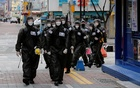 FILE PHOTO: South Korean soldiers in protective gear make their way while they disinfect buildings downtown, following the rise in confirmed cases of coronavirus disease (COVID-19) in Daegu, South Korea, March 15, 2020. REUTERS
