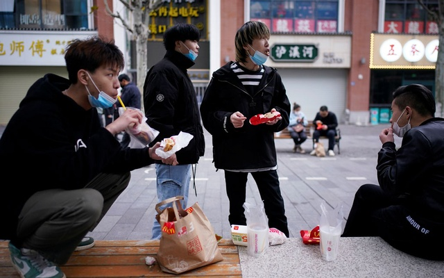 People with face masks eat outside a McDonald's restaurant in Wuhan, Hubei province, the epicentre of China's coronavirus disease (COVID-19) outbreak, Mar 30, 2020. REUTERS