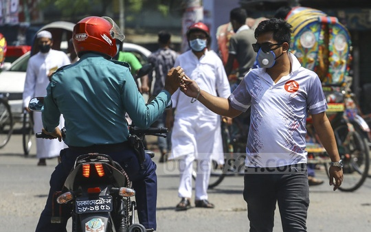 A man hands over the keys to a ride-sharing motorcycle to a police officer under the Jatrabari flyover in Dhaka. The service has helped many city-dwellers reached their destinations in cases of emergency as the city remains under a virtual lockdown amid a coronavirus outbreak. Photo: Asif Mahmud Ove