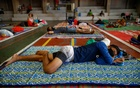Men wearing protective face masks rest on makeshift beds in a Catholic school's gymnasium which turned into a shelter for the homeless following the enforcement of a community quarantine in the Philippine main island to contain the coronavirus disease (COVID-19), in Manila, Philippines, Mar 31, 2020. REUTERS