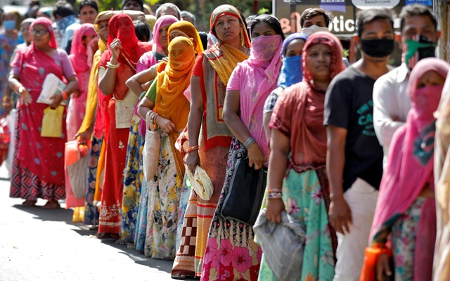 People stand in a queue as they wait for their turn to receive free food grains from a government controlled grains store during a 21-day nationwide lockdown to slow the spreading of coronavirus disease (COVID-19), in Ahmedabad, India, Apr 1, 2020. REUTERS