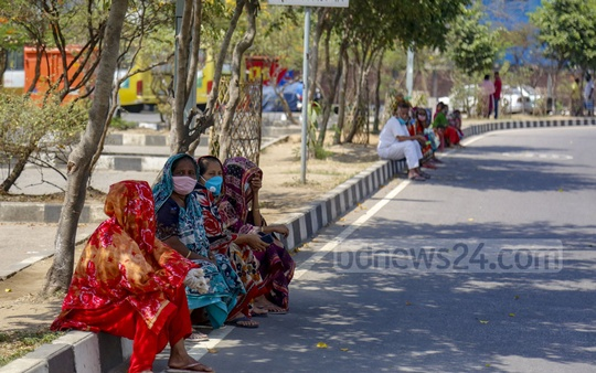 Slum residents sit on near Hatirjheel road in the hope that someone will show up with some food. Photo: Mahmud Zaman Ovi
