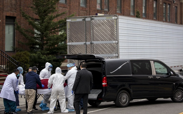 A body that had been stored in a refrigerated trailer is transferred to a hearse outside Brooklyn Hospital, in New York, March 31, 2020. Some overwhelmed funeral homes are slow to collect bodies, forcing hospitals like Brooklyn Hospital to store them in refrigerated trailers. (Dave Sanders/The New York Times)