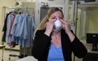 Dr Nicole McCullough, a global health and safety expert at 3M, demonstrates the correct way to put on a N95 respiratory mask at a laboratory of 3M. March 4, 2020. REUTERS