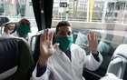 Some of the 39 Cuban doctors are seen inside a bus that will go to Andorra, at Madrid's Adolfo Suarez Barajas Airport, during the coronavirus disease (COVID-19) outbreak, Spain March 29, 2020. REUTERS