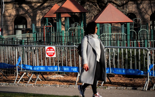 A woman walks past a barricade that is placed around a playground in Central Park, during the coronavirus disease (COVID-19) outbreak, in New York City, U.S., April 1, 2020. REUTERS