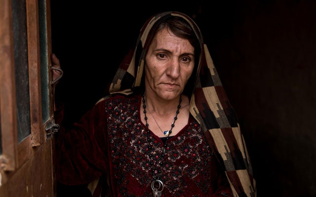 A drug addicted mother stands in the doorway of her house in Nimruz's capital Zaranj. About 10 percent of addicts are women here, the National Police estimates in Zaranj, Afghanistan on January 21, 2020. Thomson Reuters