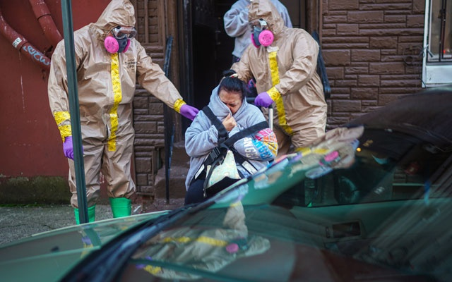 A woman in her 50s, suspected of having COVID-19, is helped from her home by Fire Department emergency medical technicians Robert Sabia, left, and Mike Pareja in Paterson, NJ, on Tuesday, Mar 24, 2020. The New York Times