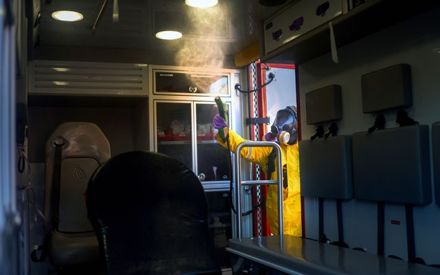 Fire Department emergency medical technician Kirk Wooten sprays decontaminants after an ambulance returns from a call involving a person under investigation for coronavirus in Paterson, NJ, on Tuesday, Mar 24, 2020. The New York Times