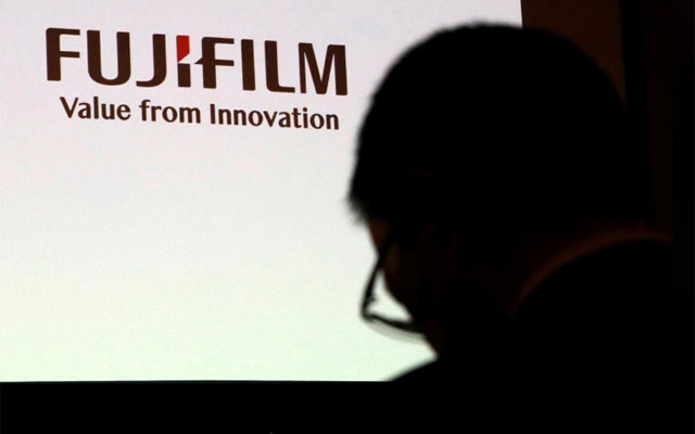 A man is silhouetted in front of Fujifilm Holdings' logo ahead of its news conference in Tokyo, Japan Jan 31, 2018. REUTERS