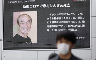 A man wearing a protective face mask, following an outbreak of the coronavirus disease (COVID-19), walks past in front of a huge screen reporting death of Japanese comedian Ken Shimura, who had been hospitalised after being infected with the new coronavirus, in Osaka, western Japan March 30, 2020, in this photo taken by Kyodo. Kyodo/via REUTERS