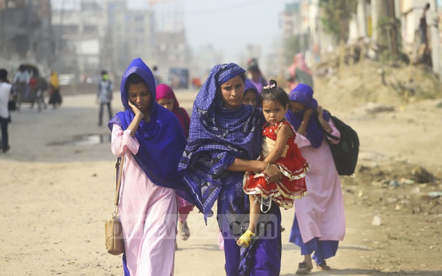 Tania, with her child on the lap, walking with her family along the Dhaka-Mymensingh Highway to reach the capital as her RMG factory is reopening on Sunday. They took truck and autorickshaw rides to reach Tongi from Mymensingh. Photo: Asif Mahmud Ove