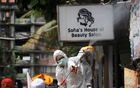 Red Cross personnel wearing protective suits spray disinfectant near a beauty salon in a densely populated neighbourhood area, amid the spread of the coronavirus disease (COVID-19) in Jakarta, Indonesia, Apr 4, 2020. REUTERS