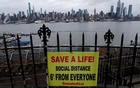 A sign promoting social distancing hangs from a fence in Hamilton Park above the Hudson River with the New York City skyline of Manhattan in the background, during the outbreak of the coronavirus disease (COVID-19), in Weehawken, New Jersey, US, April 3, 2020. REUTERS