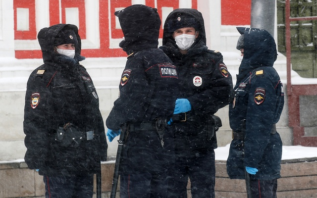 Police officers wearing protective masks gather while patrolling streets, after the city authorities announced a partial lockdown ordering residents to stay at home to prevent the spread of coronavirus disease (COVID-19), during snowfall in central Moscow, Russia Mar 31, 2020. REUTERS