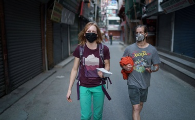 Ana Pautler, 32, and Mike Dobie, 37, from California returning to their hotel through deserted streets after collecting a free meal in Kathmandu, Nepal, Apr 2, 2020. The New York Times