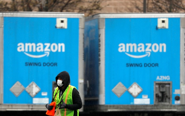 FILE PHOTO: A worker in a face mask walks by trucks parked at an Amazon facility as the global coronavirus outbreak continued in Bethpage on Long Island in New York, US, March 17, 2020. Reuters