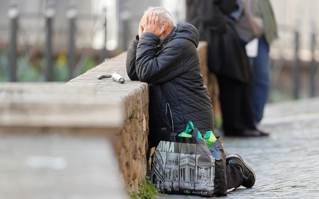 A man kneels near Saint Peter's square, as Pope Francis leads Palm Sunday mass without public participation due to the spread of coronavirus disease (COVID-19), at the Vatican, Apr 5, 2020. REUTERS