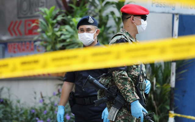 A soldier and police officer stand guard at an entrance at the City One condominium which has been placed under a lockdown after cases of coronavirus disease COVID-19 have been confirmed in the building, in Kuala Lumpur, Malaysia Mar 31, 2020. REUTERS