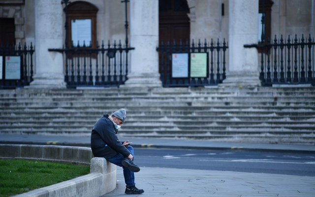A man wearing a mask sits down, as the spread of the coronavirus disease (COVID-19) continues, London, Britain, Apr 5, 2020. REUTERS