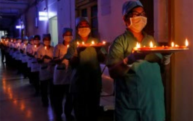 Staff members of a hospital carry candles and oil lamps to show solidarity with people who are affected by the coronavirus disease (COVID-19), and with doctors, nurses and other healthcare workers from all over the world during a 21-day nationwide lockdown to slow the spreading of the disease, in Kolkata, India, Apr 5, 2020. REUTERS