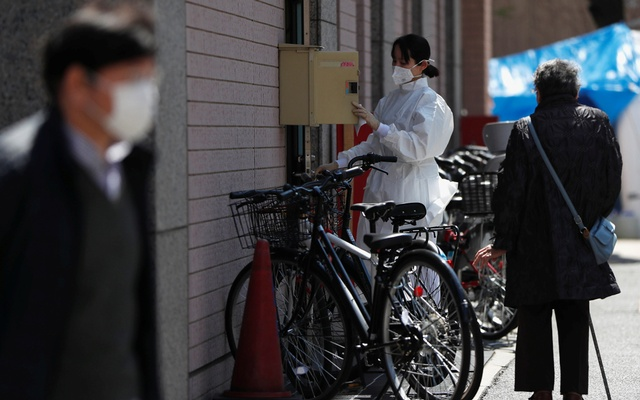 A hospital staff member wearing a protective face mask and suit, following an outbreak of the coronavirus disease (COVID-19), at the entrance of Eiju General Hospital where more than 100 people have been infected with the coronavirus, in Tokyo, Japan Apr 6, 2020. REUTERS