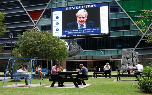 Workers take their lunch outdoors as a screen giving information about British Prime Minister Boris Johnson is seen on the background on the first day of