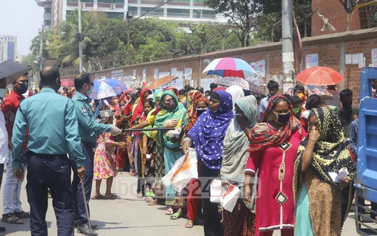 Police personnel wield their batons as people were reluctant to maintain safe distance from each other while waiting in the queue to buy subsidised rice at Tk 10 per kg in Dhaka. Photo: Asif Mahmud Ove