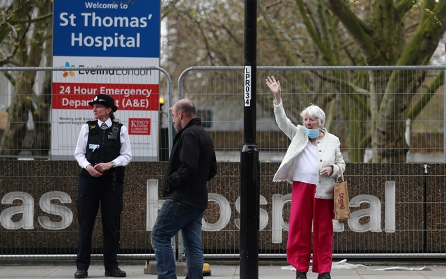 A woman wearing a protective face mask is seen outside St Thomas' Hospital in London after British Prime Minister Boris Johnson was admitted to hospital for tests on Sunday after suffering persistent coronavirus (COVID-19) symptoms after testing positive for the virus. London, Britain, April 6, 2020. Reuters