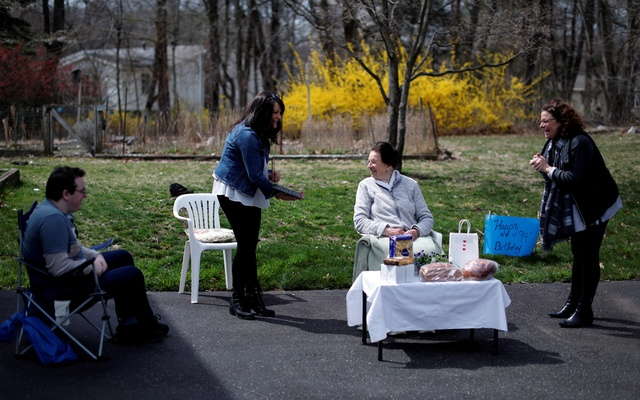 Sisters Sylvia (R), Stephanie Falcomer and grandson Peter Henry hold a 'socially distant' 94th birthday party in their driveway for their mother and grandmother Marcella Falcomer, who came to America from Italy in 1955, as they say hello to their relatives on a Zoom video conference call during the outbreak of the coronavirus disease (COVID-19) in West Nyack, New York, US, April 5, 2020. Reuters