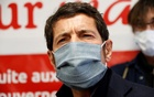 Cannes Mayor David Lisnard, wearing a protective face mask, talks to the media as an employee checks the temperature of visitors at the entrance of a Carrefour market in Cannes as the spread of the coronavirus disease (COVID-19) continues in France, Apr 8, 2020. REUTERS