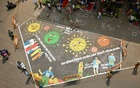 Police officers stand around a graffiti on a road depicting coronavirus to create awareness about social distancing during a 21-day nationwide lockdown to slow the spreading of coronavirus disease (COVID-19), in Chennai, India, Apr 9, 2020. REUTERS