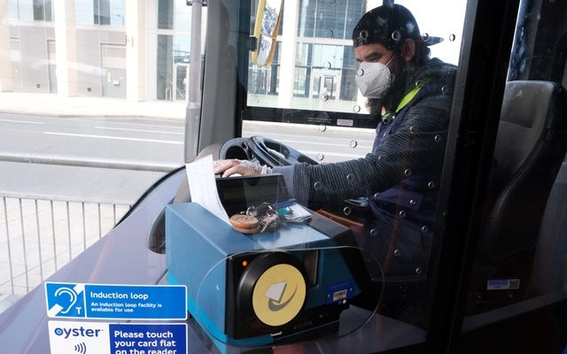 A bus driver is pictured on a bus wearing a protective face mask in Canning Town as the spread of the coronavirus disease (COVID-19) continues, in London, Britain, April 8, 2020. REUTERS
