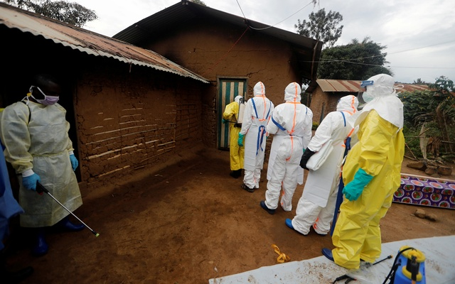 FILE PHOTO: Kavota Mugisha Robert (L), a healthcare worker who volunteered in the Ebola response, stands with decontamination gear as his colleague prepare to enter a house where a woman, 85, is suspected of dying of Ebola in the Eastern Congolese town of Beni in the Democratic Republic of Congo, October 8, 2019. REUTERS/Zohra Bensemra/File Photo