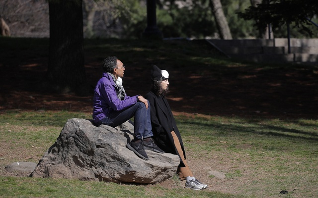 Two people sit on a rock in the sun nearby a newly constructed field hospital in the East Meadow of Central Park during the outbreak of the coronavirus disease (COVID-19) in the Manhattan borough of New York City, New York, US, April 1, 2020. Reuters