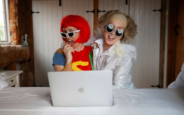 Emily dressed as Elton John and Molly as Lady Gaga watch the concert One World: Together At Home, as the spread of the coronavirus disease continues, in Henton, Britain. REUTERS