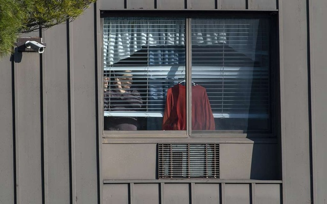 A resident looks through a window at Andover Subacute and Rehabilitation Center in Andover, NJ, on Sunday, April 19, 2020.