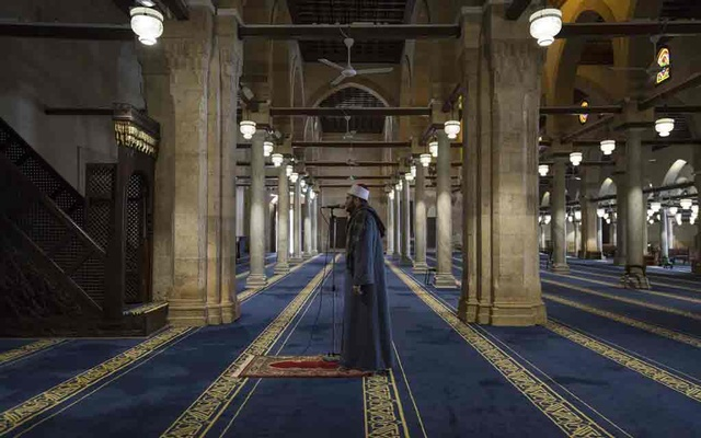 A muezzin issues a call to prayer at the empty Al-Azhar mosque, which opened in AD 972, in Cairo, April 18, 2020. The New York Times